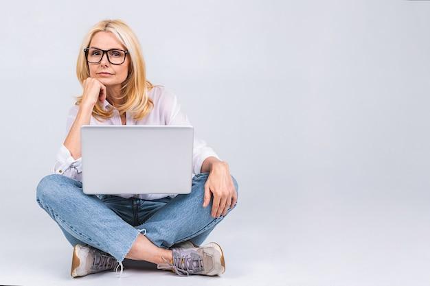 Pomysł na biznes. piękna starsza dojrzała kobieta z laptopem siedząca na podłodze w pozycji lotosu ze zmęczoną i znudzoną miną.