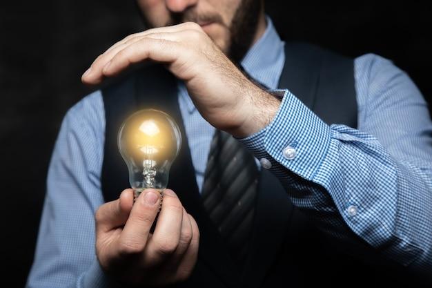 Pomysł na koncepcję. mężczyzna chroni żarzącą się lampę na szarej powierzchni