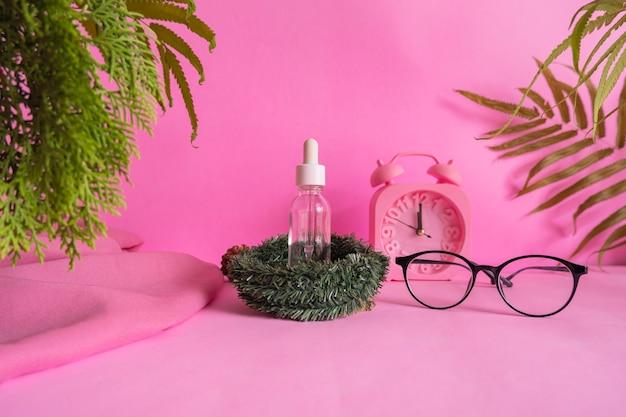 Pomysł na minimalistyczną koncepcję butelki kosmetycznej na różowym tle z dekoracją budzika, liśćmi i okularami