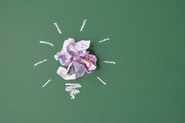 Pomysł na oszczędzanie pieniędzy. zmięty papier banknotów dolarowych w postaci żarówek na tle zielonej chal pokładzie k