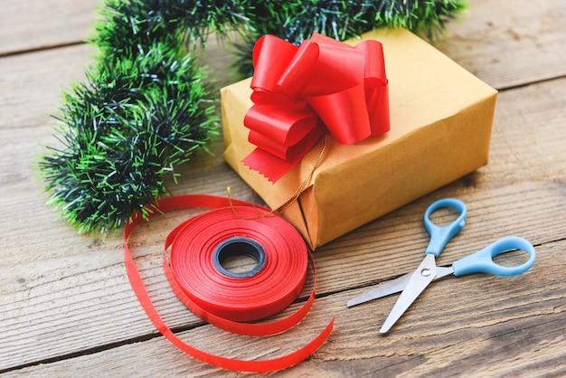 Pomysł na prezent dla majsterkowiczów / domowe zapakowane prezenty świąteczne z narzędziami i dekoracjami na drewnianym pudełku upominkowym diy hobby owiniętym brązowym papierem na boże narodzenie lub nowy rok