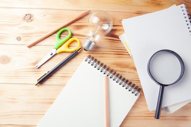 Pomysł na studium koncepcji. lupa, notatnik, lampka i długopis na pulpicie