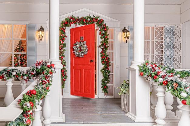 Pomysł na świąteczną dekorację ganku. wejście do domu z czerwonymi drzwiami ozdobionymi na święta. czerwony i zielony wieniec wieniec z gałęzi jodły i światła na balustradzie. wigilia w domu.