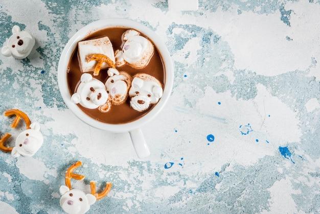 Pomysł na świąteczną przekąskę dla dzieci, gorącą czekoladę z misiami i ptasie mleczko z jelenia. na jasnej powierzchni skopiuj widok z góry miejsca