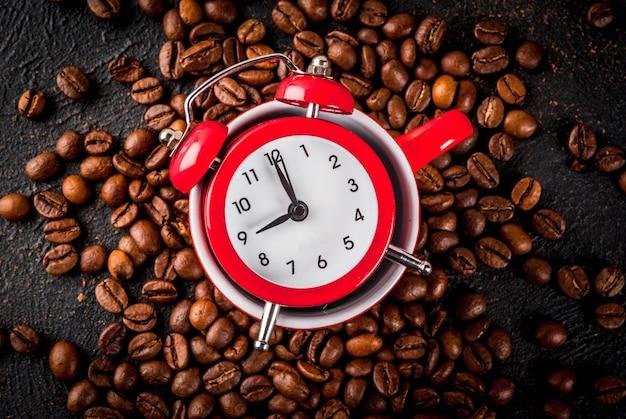 Pomysł na wesoły, dobry początek dnia, poranną kawę. ciemne tło zardzewiały z ziaren kawy, budzik i filiżankę kawy. widok z góry