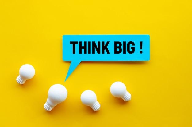 Pomyśl na wielką skalę, świetny pomysł, koncepcje kreatywności biznesowej z żarówką i tekstem na żółtym tle.