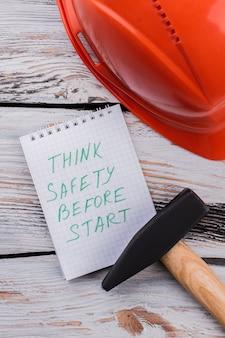 Pomyśl o bezpieczeństwie przed rozpoczęciem notatek i narzędzi roboczych na drewnianym stole. widok z góry na płasko.