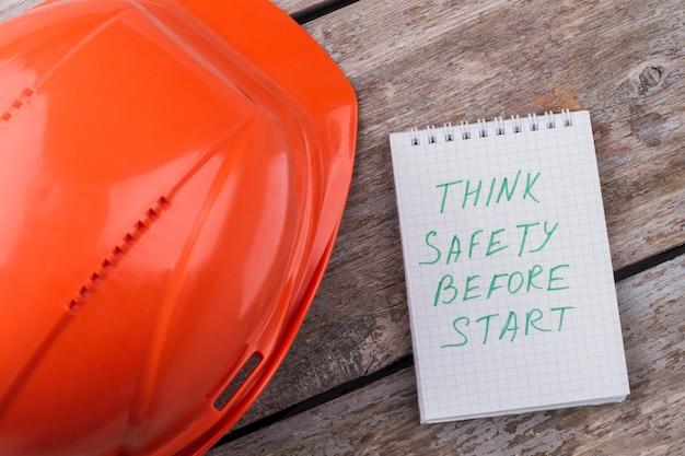 Pomyśl o bezpieczeństwie przed rozpoczęciem pracy. kask budowniczy i notatnik. płaski widok z góry.