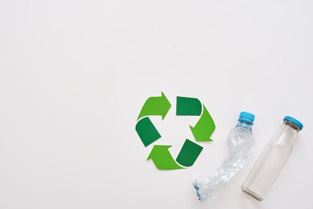 Pomyśl o ekologii na białym tle symbolu recyklingu i zgniataniu plastikowych butelek