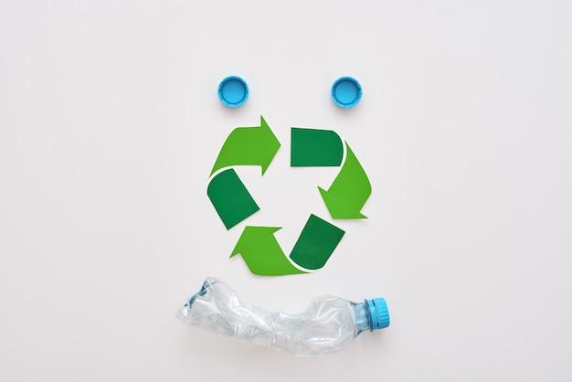 Pomyśl o ekologii na białym tle symbolu recyklingu i zmiętej plastikowej butelce