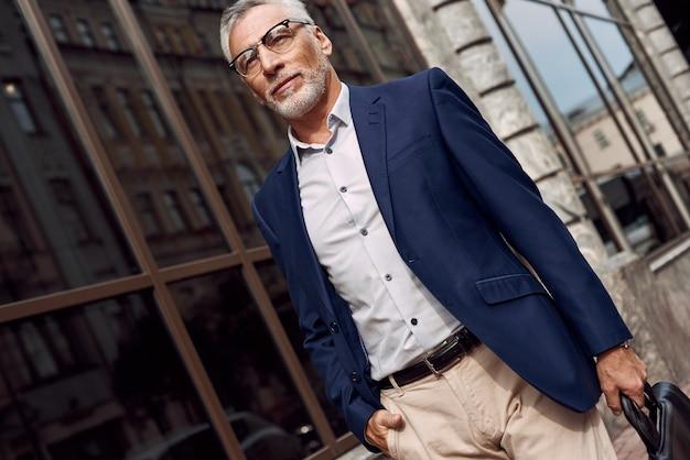 Pomyśl o spotkaniu biznesowym elegancki mężczyzna w swobodnym garniturze uśmiechający się podczas spaceru na świeżym powietrzu