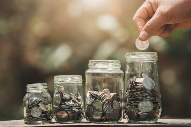 Pomysł oszczędzania pieniędzy ręcznie wkładanie monet do dzbanka szklanego