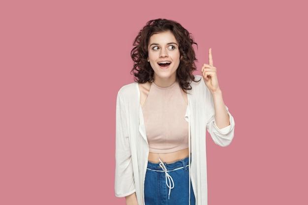 Pomysł. portret zaskoczony piękna brunetka młoda kobieta z kręconymi fryzurami w stylu casual stojący, trzymając palec w górze i podekscytowany nowym pomysłem. kryty studio strzał na białym tle na różowym tle.