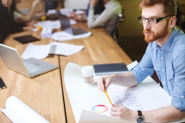 Pomysł. projektant siedzący obok biurka w nowoczesnym studio