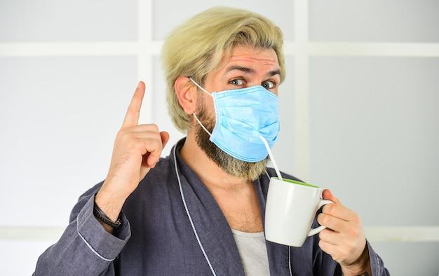 Pomysł. szpital lub zanieczyszczenia chronią maskowanie twarzy. maska medyczna jako ochrona przed koronami. człowiek pić kawę w masce ochronnej respiratora. wybuch pandemii koronawirusa. maska oddechowa do oddychania lekarza.