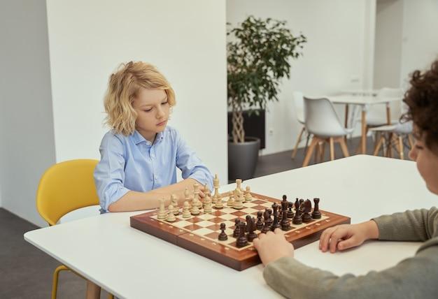 Pomyśl zanim zaczniesz działać zamyślony mały kaukaski chłopczyk grający w szachy ze swoim przyjacielem siedzącym razem