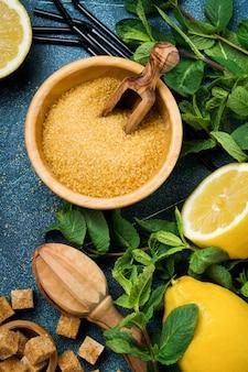 Pomysł ze składnikami domowej orzeźwiającej lemoniady z sokiem cytrynowym, cukrem trzcinowym i miętą na starej betonowej powierzchni