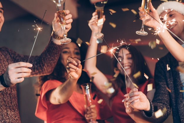Pomyśl życzenie. wielorasowi przyjaciele świętują nowy rok i trzymają lampki bengalskie i szklanki z napojem