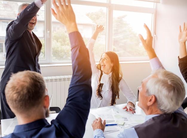 Pomyślna biznes drużyna podnosi ich ręki przy miejscem pracy