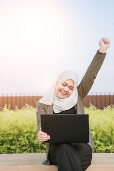 Pomyślna biznesowa azjatykcia muzułmańska kobieta w zielonym kostiumu i działanie na komputerze przy parkiem.