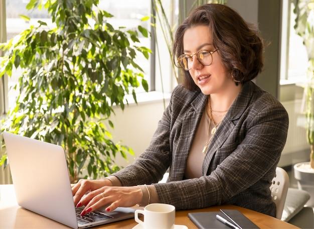 Pomyślna biznesowa kobieta pisać na maszynie na komputerowym surfuje sieci patrzeje ekran cieszy się daleką pracę.