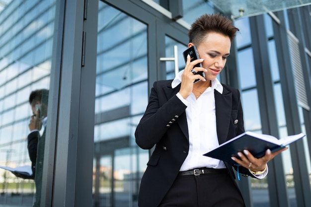 Pomyślna biznesowa kobieta pozuje telefon i opowiada