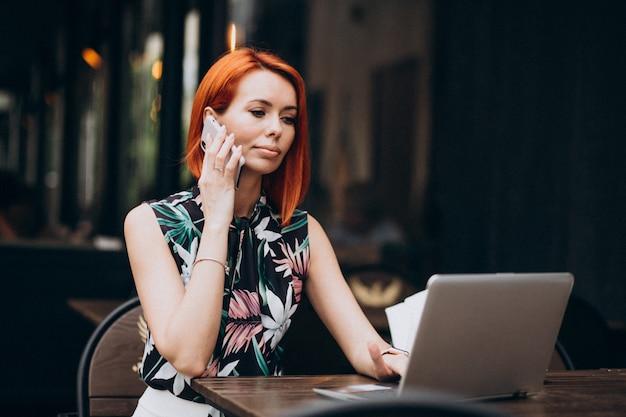 Pomyślna biznesowa kobieta pracuje na laptopie w kawiarni