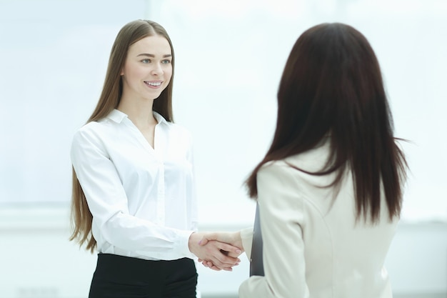 Pomyślna biznesowa kobieta uścisk dłoni z pracownikiem.