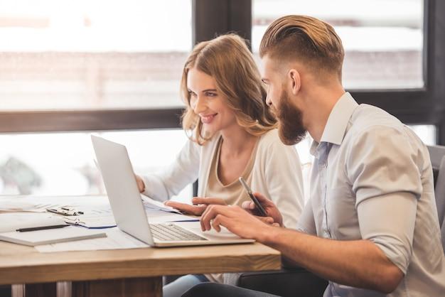 Pomyślna biznesowa para używa laptop