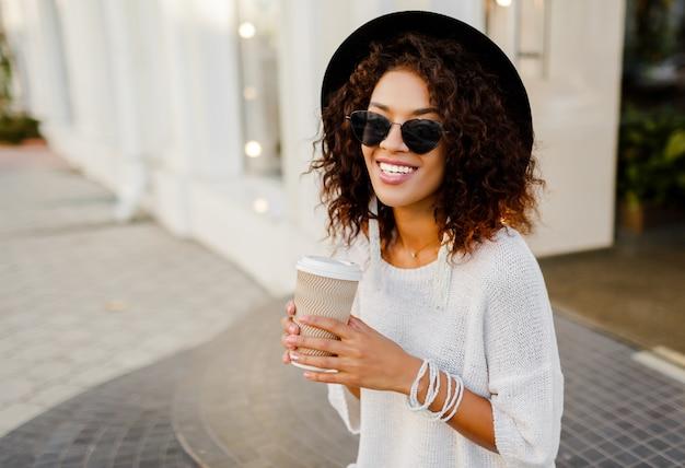 Pomyślna czarna kobieta, bloger lub kierownik sklepu rozmawia przez telefon komórkowy podczas przerwy na kawę. siedząc na schodach i trzymając papierowy kubek gorącego napoju.