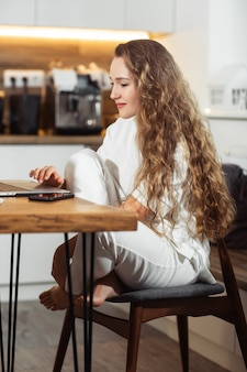 Pomyślna dziewczyna śmia się i pracuje w domu. piękna stylowa kobieta uśmiechnięta i relaksuje w domu. bizneswoman przedsiębiorca pracuje na laptopie z domowego biura
