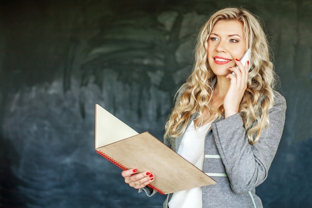 Pomyślna kobieta opowiada na telefonie. studencka koncepcja edukacji