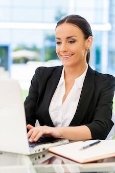 Pomyślna kobieta. piękna młoda kobieta w stroju formalnym pracuje na laptopie i uśmiecha się siedząc przy stole na zewnątrz