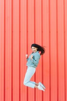Pomyślna kobieta skacze przed kruszcowym textured tłem
