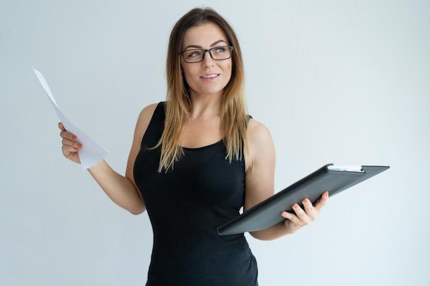 Pomyślna ładna kobiety mienia kartoteka, dokument i patrzeć daleko od.
