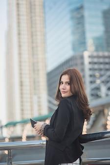 Pomyślna mądrze biznesowa kobieta patrzeje ufny i uśmiechnięty mienie pastylki komputer