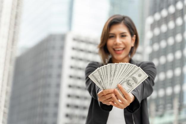 Pomyślna piękna azjatycka biznesowa kobieta trzyma pieniądze dolarów amerykańskich rachunki w ręce, biznesowy pojęcie