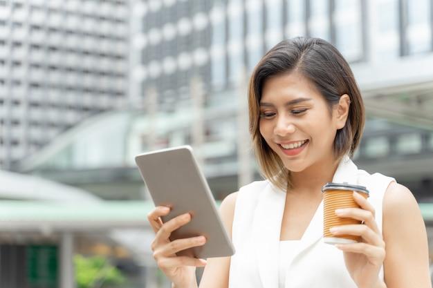 Pomyślna piękna azjatykcia biznesowa młoda kobieta używa mądrze telefon i filiżankę w ręce