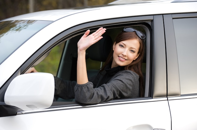 Pomyślna piękna młoda kobieta w nowym samochodzie