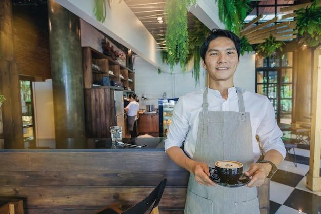 Pomyślna przystojna właściciel biznesu pozycja z filiżanką kawy przed barem.