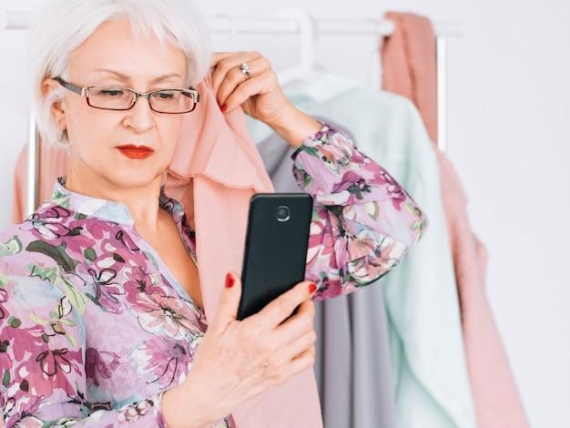 Pomyślna starsza kobieta. biznesowy butik mody. starsza pani robi selfie podczas analizy typu koloru.