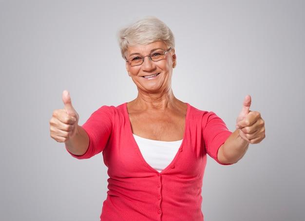 Pomyślna starsza kobieta z kciukiem do góry