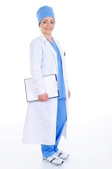 Pomyślna wesoła kobieta chirurg w szpitalnej sukni z dokumentami