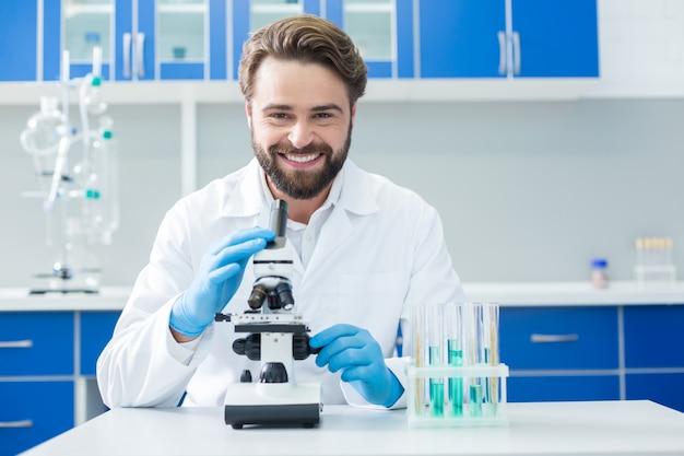 Pomyślne badania. szczęśliwy pozytywnie zachwycony naukowiec siedzący przed mikroskopem i uśmiechający się, ciesząc się ze swoich badań