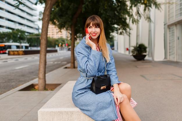 Pomyślne uśmiechnięta blond kobieta rozmawia przez telefon komórkowy na ulicy