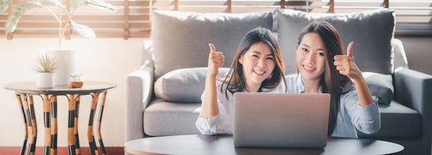 Pomyślni kobieta najlepsi przyjaciele używa laptop