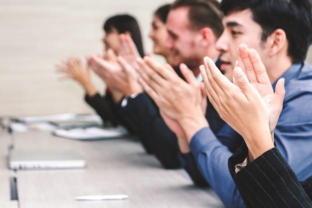 Pomyślni ludzie biznesu klascze ręki w spotkaniu