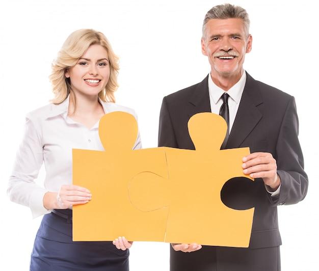 Pomyślni ludzie biznesu, którzy chcą umieścić dwa duże kawałki.