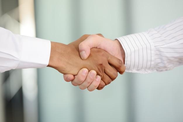 Pomyślni ludzie biznesu wręczają potrząśnięcie po wielkiej oferty