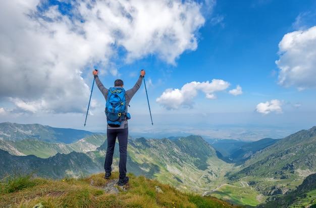 Pomyślny aktywny mężczyzna wycieczkowicz na szczycie góry cieszy się widok. koncepcja stylu życia sport podróż